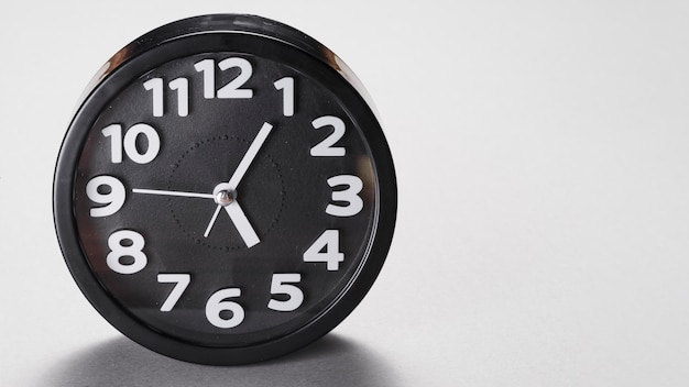 Round shape black alarm clock on gray background Free Photo