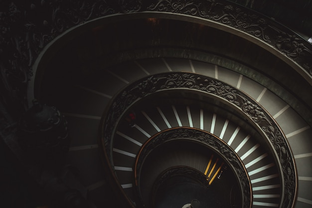 Round staircase in a vatican museum leading visitors to look at christian works of art Free Photo