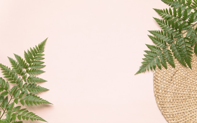 Round wicker stand and palm leaves on pink wall. flatlay eco style concept with text place Premium Photo