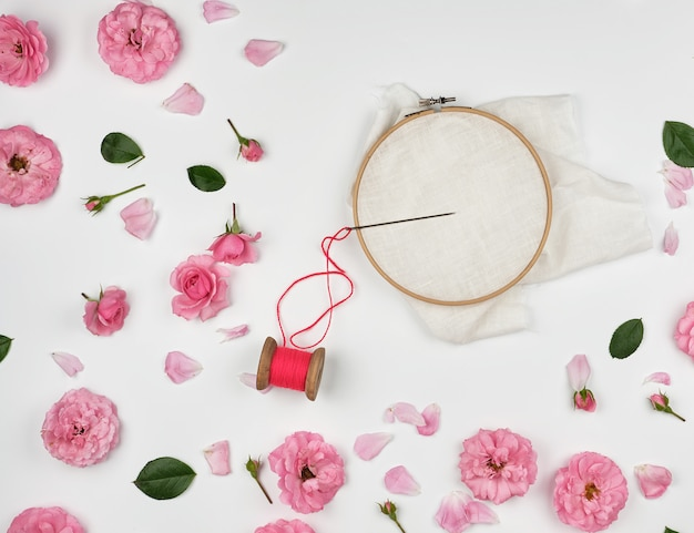 Round wooden hoop and red thread with needle Premium Photo