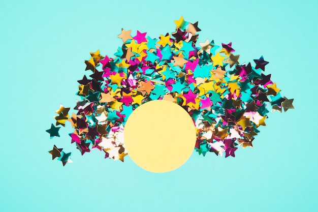 Round yellow frame surrounded with colorful star confetti on blue background Free Photo