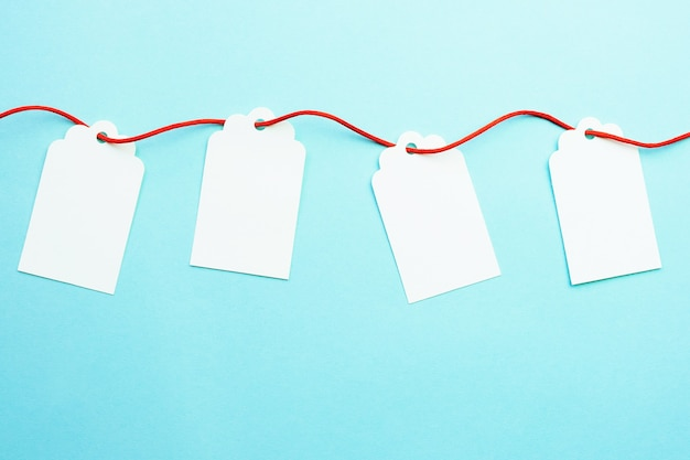 Row of blank gift tags mock-ups on red ribbon string on blue Premium Photo