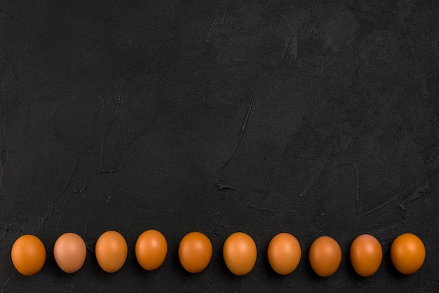 Row of brown chicken eggs on table Free Photo