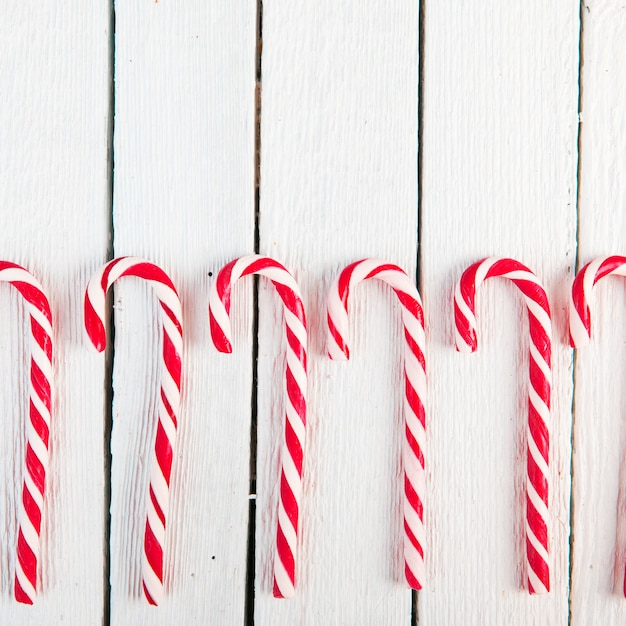 Row of candy canes on wood desk Free Photo