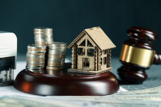 A row of coins on a small house model and a law auction hammer Premium Photo