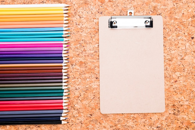 Row of color pencils and clipboard on cork background overhead Free Photo