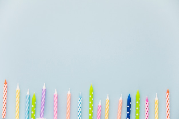 Row of colorful candles at the bottom of the blue background Free Photo