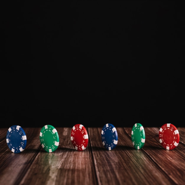 Row of colorful casino chips on wooden surface Free Photo