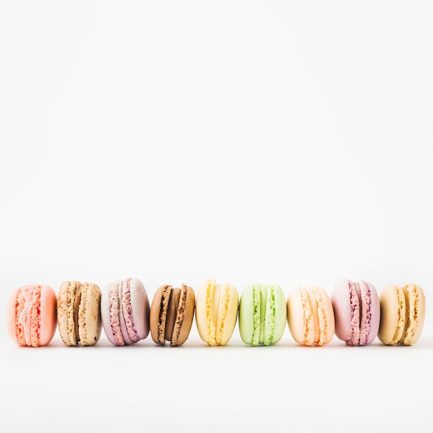 Row of colorful macaroons isolated on white background Free Photo