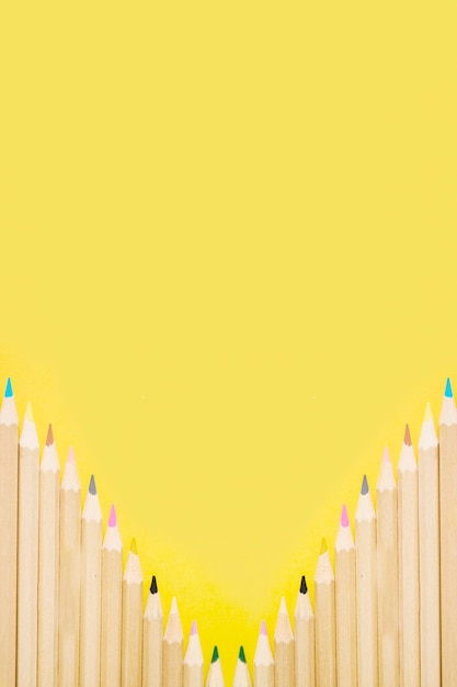 Row of colorful pencils on yellow background Free Photo