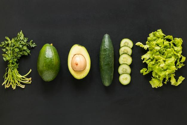 Row coriander; avocado; cucumber and lettuce arranged on black backdrop Free Photo