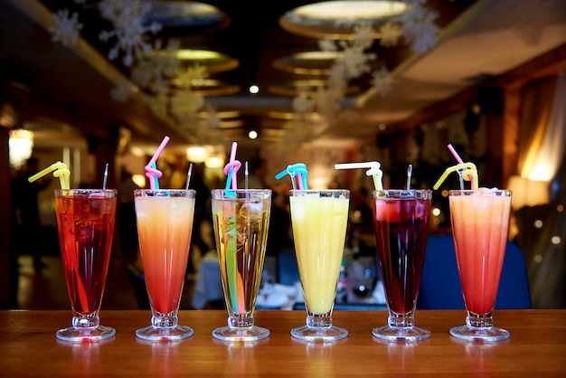 Row of different cocktails with straws Premium Photo