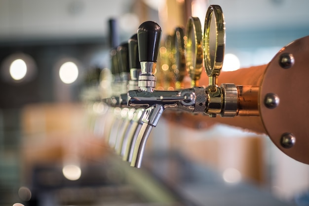 Row of draft beer tab on the top of counter bar in closeup view, time of celebration. Premium Photo