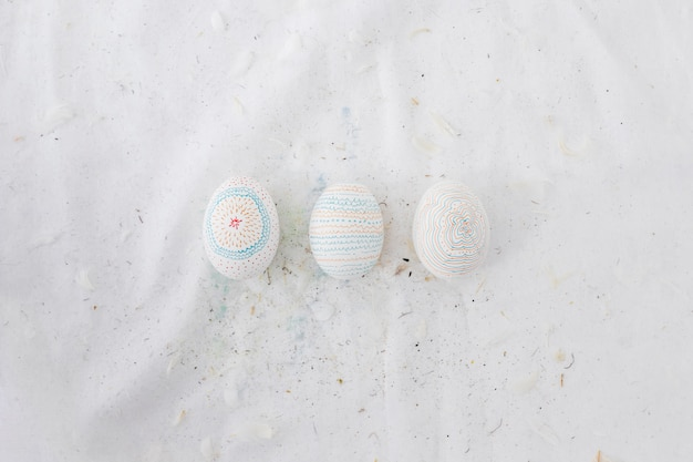 Row of easter eggs with patterns and feathers on textile Free Photo