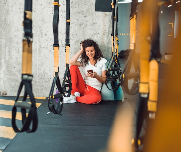 Row of fitness strap in front of woman listening to music on smartphone Free Photo