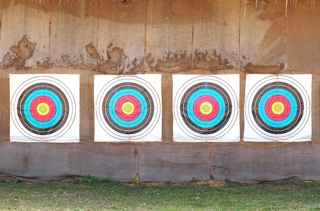 Row of four archery target rings on old brown fabric background. Premium Photo