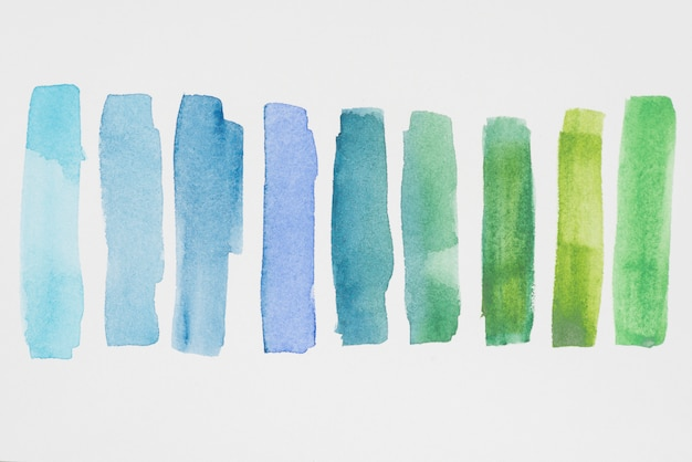 Row of green and blue paints on white paper Free Photo