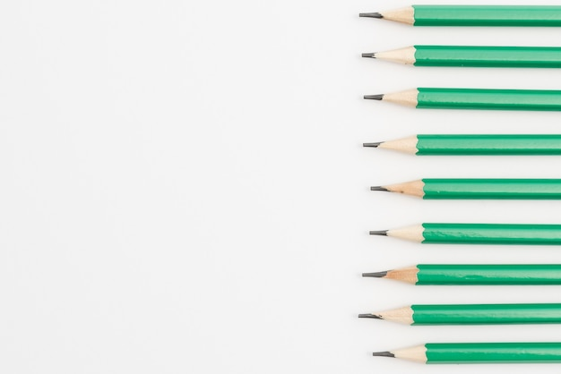Row of green sharp pencils on white background Free Photo