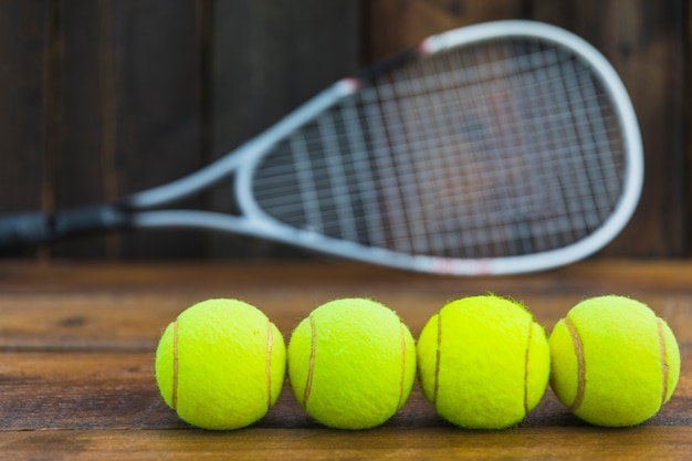 Row of green tennis balls in front of blurred racket on wooden table Free Photo