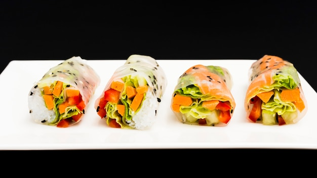 Row of healthy spring rolls on plate Free Photo