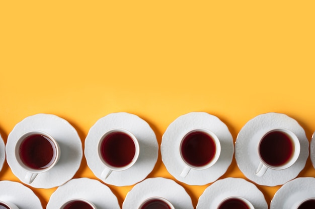 Row of herbal white tea cup on yellow background Free Photo