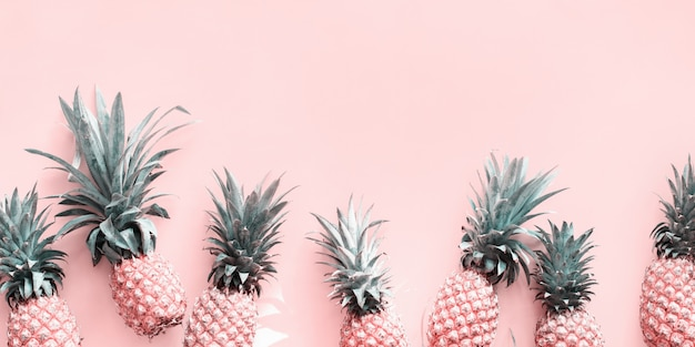 Row line pine apple whole tropical fruits pink Premium Photo