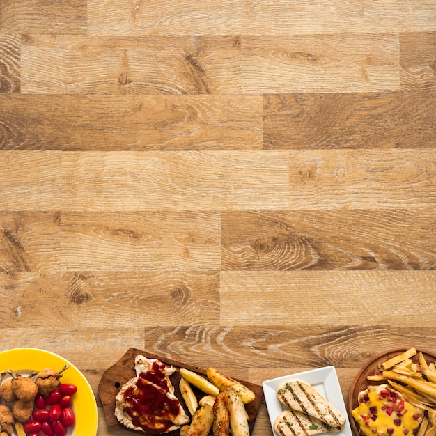Row made of chicken fast food meal on wooden table Free Photo