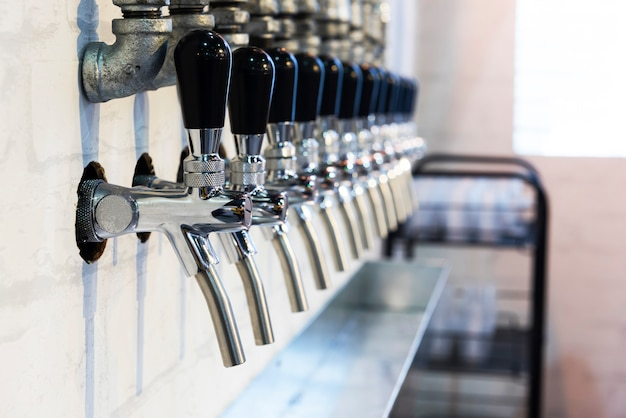 Row of metal spigots for drink testing Premium Photo