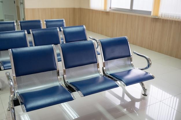 Ряд алюминиевого синего скамейки в приемной больницы Premium Фотографии
