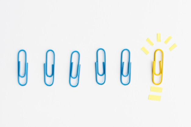 青いクリップの行は、アイデアの概念を示す黄色のペーパークリップの近くに配置します。 Premium写真