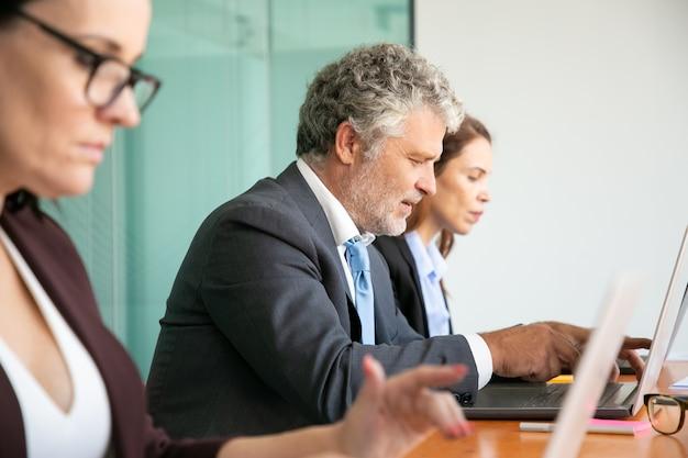 オフィスでコンピューターを使用しているビジネス人々の行。ノートパソコンのキーボードで入力するさまざまな年齢の従業員。 無料写真