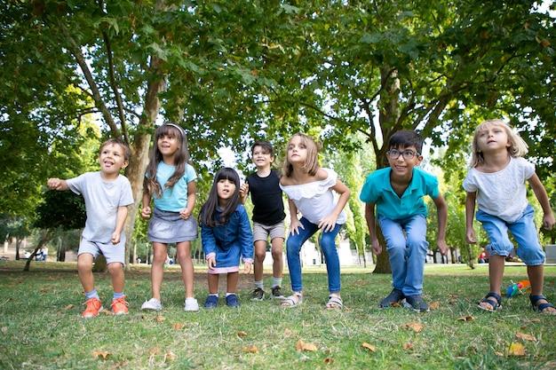흥분에 멀리 찾고 공원에서 함께 웅크 리고 명랑 한 아이의 행. 키즈 파티 또는 엔터테인먼트 개념 무료 사진