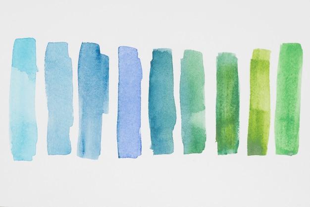白い紙に緑色と青色の塗料の行 Premium写真