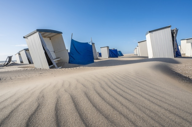 Ряд индивидуальных белых шкафчиков раздевалки и кабинки для переодевания на песчаном пляже Бесплатные Фотографии