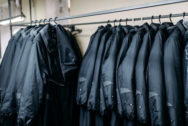 Ряд курток на вешалках, магазине одежды, швейной фабрике или ткани платья. одежда на вешалках Premium Фотографии
