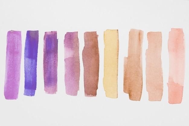 白い紙の紫色と茶色の塗料の行 Premium写真