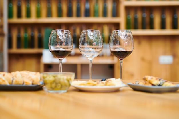 Ряд бокалов с красным вином и закусками рядом, приготовленные для сомелье в подвале ресторана Premium Фотографии