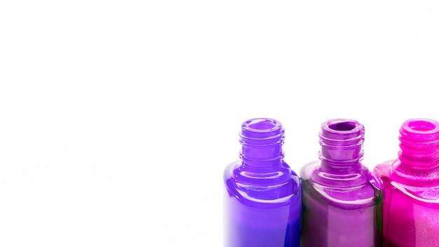 Row of open color nail polish for manicure or pedicure on white backdrop Free Photo