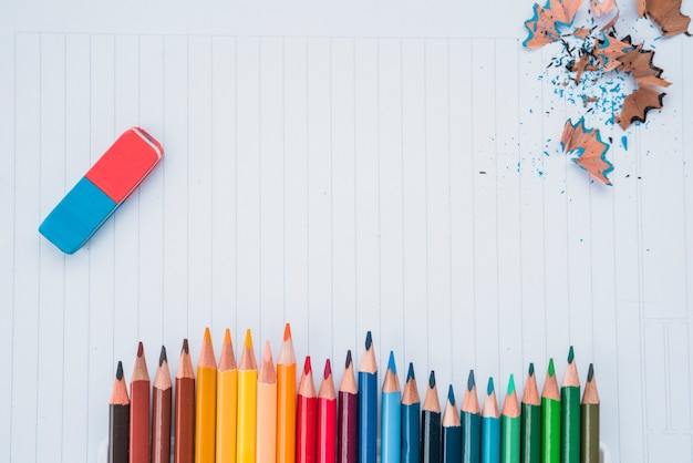 Row of pencil colors with eraser and pencil shaving on white paper Free Photo