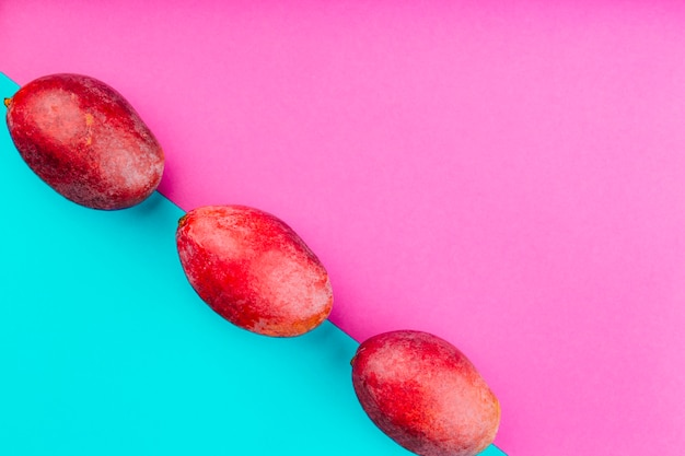 Row of red mangoes on dual pink and blue background Free Photo