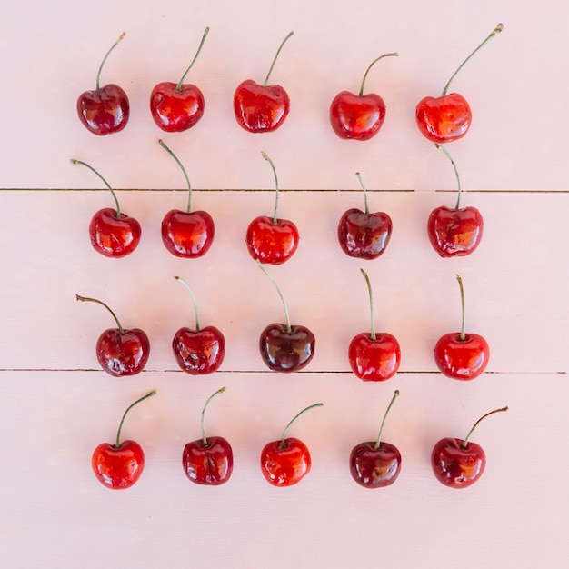 Row of ripe juicy cherries on pink wooden background Free Photo