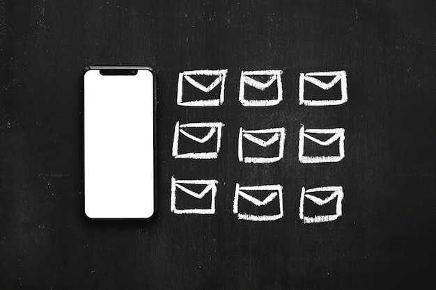 Row of small drawn messages icon near the cellphone on chalkboard Free Photo