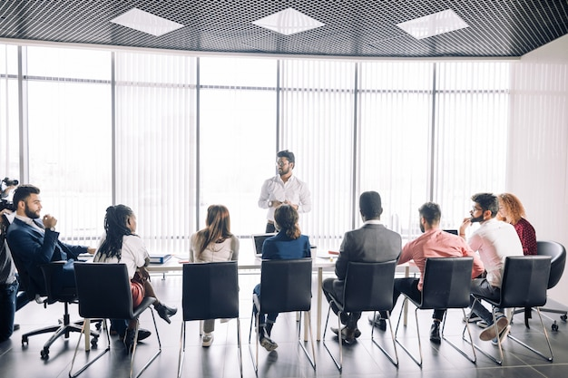 Row of unrecognizable business people sit in conference hall at business event. Premium Photo