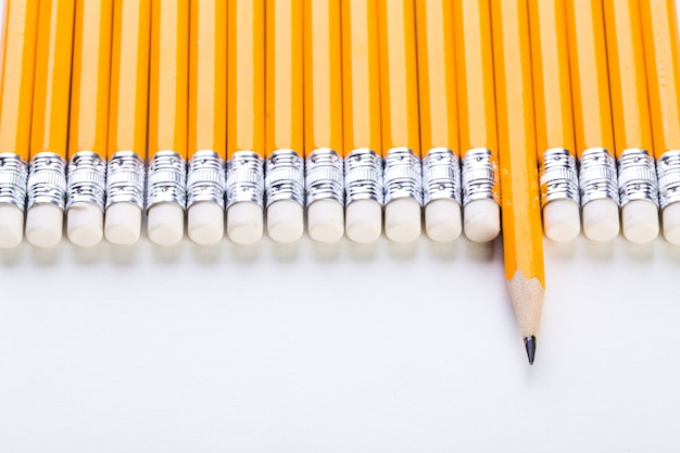Row of yellow pencils with one sticiking out on white wall, business and leadership concept Premium Photo
