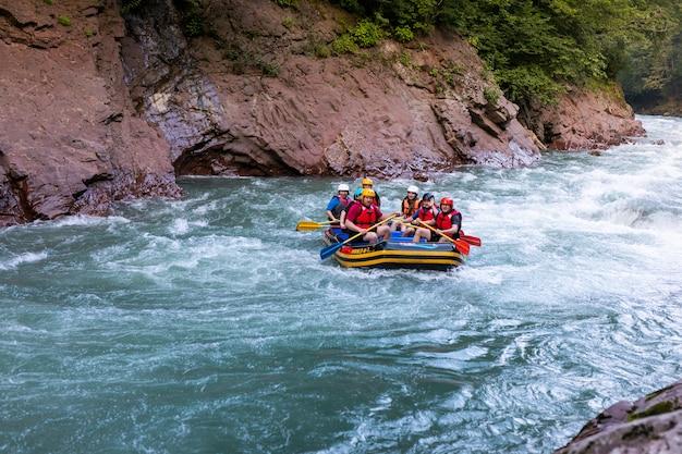 ガイドホワイトウォーターラフティングと川でのrowぎで幸せな人々のグループ。 Premium写真