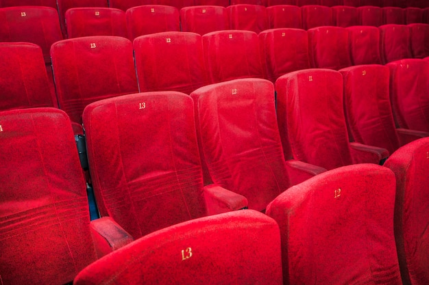 Rows of comfortable red chairs in cinema Free Photo