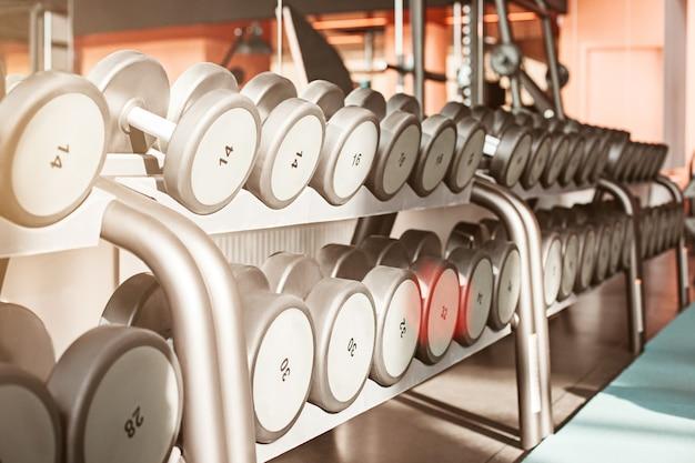 Righe di manubri in palestra con contrasto alto e tonalità di colore monocromatico Foto Gratuite