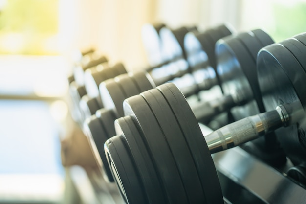 Rows of metal dumbbells on rack in the gym or sport club. Premium Photo