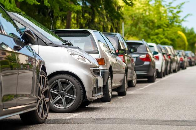 住宅街の道端に駐車した車の列。他の車の間に駐車した小型車。 Premium写真