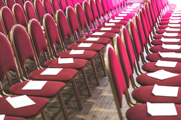 Rows of red chairs in conference hall, empty meeting or event room. empty guest seats. Premium Photo